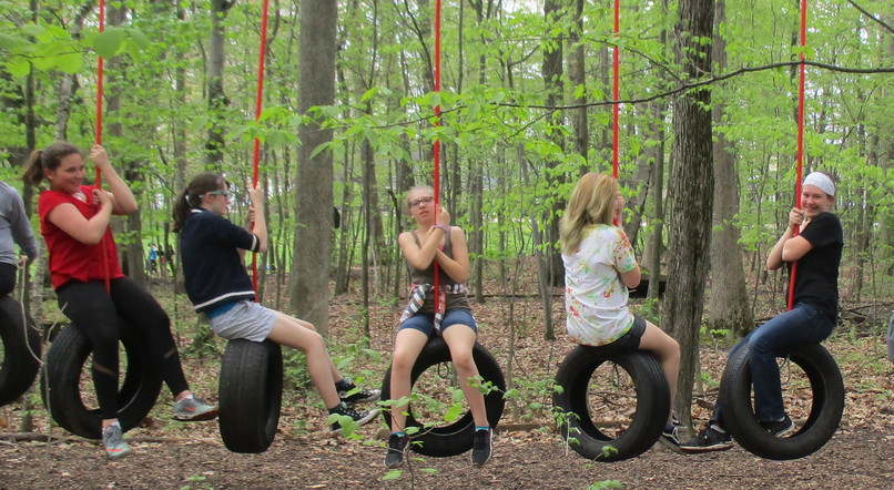 Students hanging on tire swings